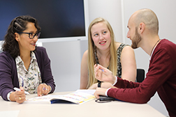 Three people at a desk, talking with eachother. Photo: Universität Osnabrück/Reimar Ott